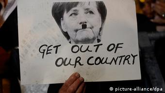 Protestor holds placard showing Angela Merkel with Hitler moustache