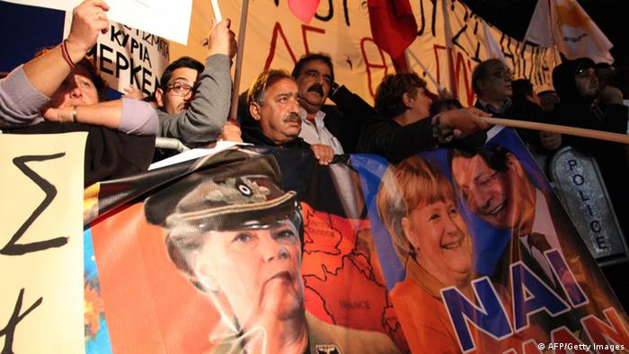 Cypriot protestors wave banners picturing German Chancellor Angela Merkel and Cypriot President Nicos Anastasiades during a demonstration against an EU bailout deal outside the parliament in the capital, Nicosia, on March 19, 2013. Copyright: AFP PHOTO/BARBARA LABORDE
