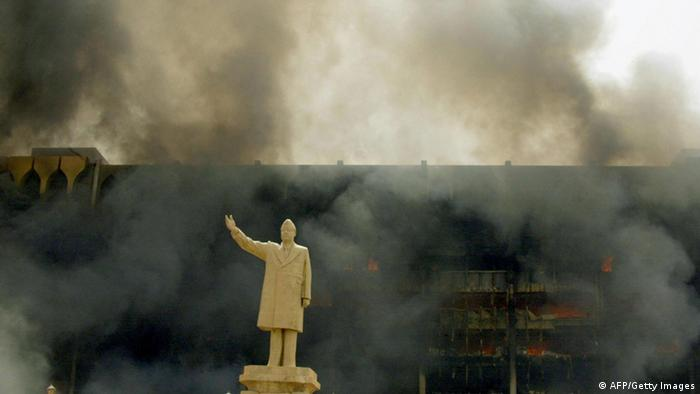A statue of Iraqi President Saddam Hussein stands in front of the burning building of the Iraqi Olympic Committee