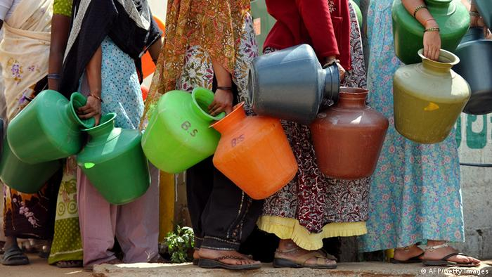 Indian residents in a district facing a drinking water shortage wait with plastic pots at a community tube well to collect drinking water in Bangalore on October 8, 2012. T
