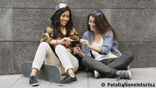 Two sitting girls are looking at their smartphones