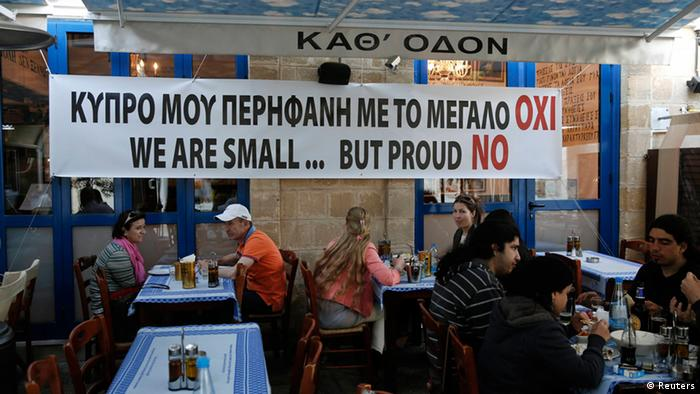 People eat at a restaurant under a banner placed by the owner in central Nicosia (Photo: Karahalis/DW)