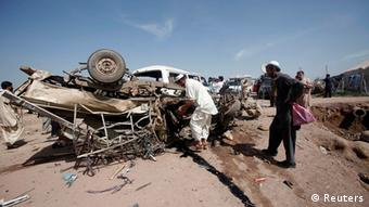 Security officials collect evidence from a damaged vehicle in Jalozai camp REUTERS/Fayaz Aziz