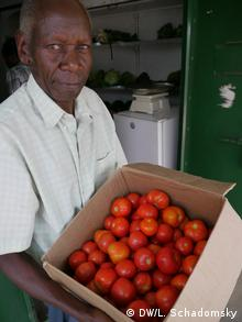 Ssozi Muwangwa holding a box of tomatoes