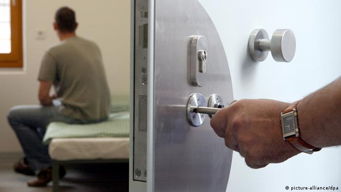 ARCHIV - ILLUSTRATION - Ein Justizbeamter schließt am 05.09.2007 einen Häftling in seinen Haftraum