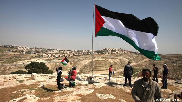 Palestinians hoist a huge Palestinian flag close to Israel's largest Jewish settlement of Maale Adumin on the outskirts of Jerusalem where the US President Barak Obama is visiting on March 20, 2013, on the first day of his three day visit. AFP PHOTO/ ABBAS MOMANI (Photo credit should read ABBAS MOMANI/AFP/Getty Images)