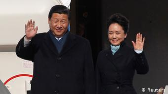 Chinese President Xi Jinping (L) and First Lady Peng Liyuan wave as they disembark from a plane upon their arrival at Moscow's Vnukovo airport March 22, 2013. REUTERS/Maxim Shemetov (RUSSIA - Tags: POLITICS TRANSPORT)