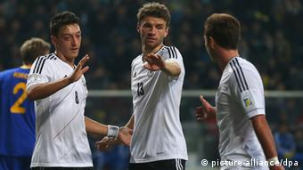 GettyImages 164296314 ASTANA, KAZAKHSTAN - MARCH 22: Thomas Mueller (C) of Germany celebrates scoring the 4th team goal with his team mates Mesut Oezil (L) and Mario Goetze (R) during the FIFA 2014 World Cup qualifier group C match between Kazakhstan and Germany at Astana Arena on March 22, 2013 in Astana, Kazakhstan. (Photo by Alexander Hassenstein/Bongarts/Getty Images)