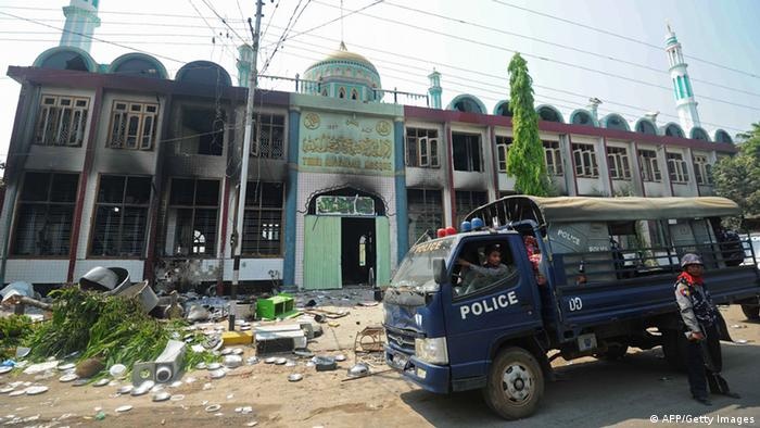 GettyImages 164264830 Policemen stand guard outside a partially-burnt mosque in riot-hit Meiktila, central Myanmar on March 22, 2013.