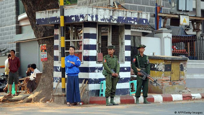 GettyImages 164363139 Armed soldiers stand guard in a street in riot-hit Meiktila, central Myanmar on March 23, 2013. Troops patrolled the streets of a central Myanmar town on March 23 after Buddhist-Muslim unrest tore through the area leaving at least 20 dead and spurring the government to declare emergency rule. AFP PHOTO/Soe Than WIN (Photo credit should read Soe Than WIN/AFP/Getty Images)