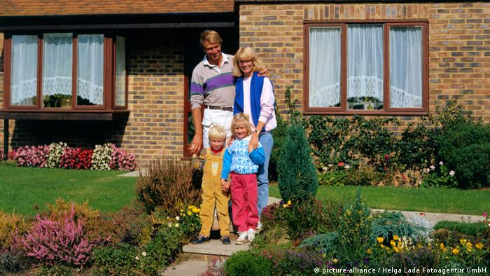 A family stands in front of their home (Photo: picture-alliance/Helga Lade Fotoagentur GmbH)