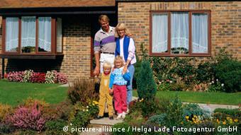 Семья с детьми на фоне своего дома