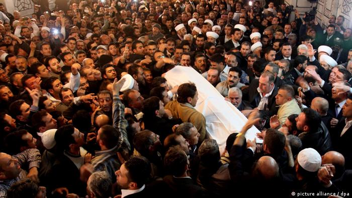 epa03637867 The coffin of Syria's late top Sunni Muslim preacher, Sheik Mohammad Said Ramadan al-Buti, wrapped with a white blanket, is held on the shoulders of mourners amid shouts of God is Great, at the Umayyad Mosque in Damascus, Syria, 23 March 2013. Aal-Buti and his grandson were killed, along with 47 others, in a suicide attack that ripped through a mosque in Damascus on 21 March. Al-Buti, 84, a prolific writer whose sermons were regularly broadcast on TV. He was a vocal supporter of the Syrian regime. EPA/YOUSSEF BADAWI