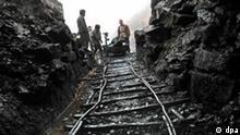 China Arbeitsbedingungen Arbeiter einer Kohlegrube in Pingba im Südwesten Chinas wiegen am 5.1.2004 am Ausgang eines Schachts die nach oben beförderte Kohle.