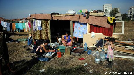 A Roma family wash clothes in a makeshift camp, built near the huge holed-out shell of an apartment building and the pungent stench of tons of rubbish, of the so-called 'Building 20' on the outskirts of the town of Yambol, Bulgaria. Photo DIMITAR DILKOFF/AFP/Getty Images