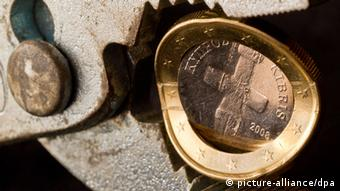 A Cyprus EU coin being squeezed by a pair of pliers Copyright: Patrick Pleul/dpa