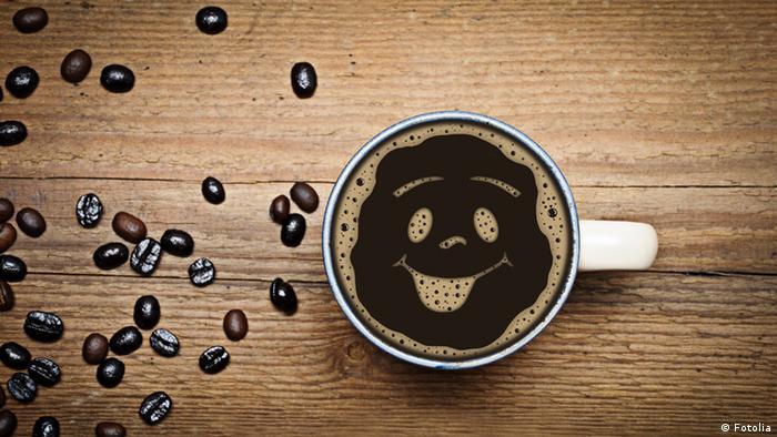 Eine Tasse mit Kaffee und einem Smiley-Gesicht. Drumherum liegen Kaffeebohnen