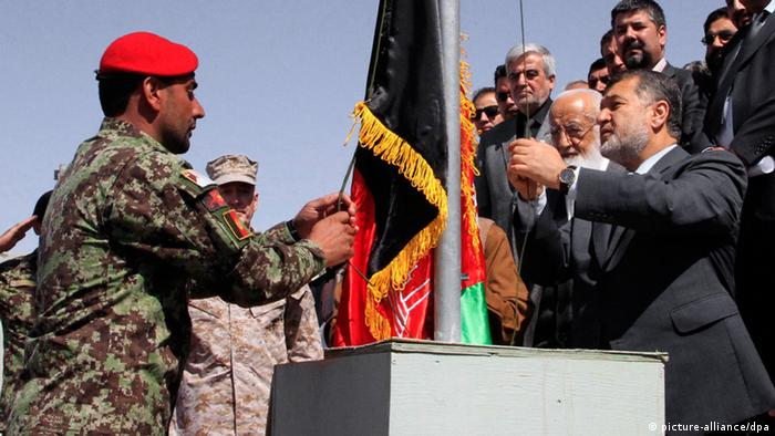Bismillah Muhammadi (R) Afghan Defense Minister raises national flag during the Bagram Prison handover ceremony, on the outskirts of Kabul, Afghanistan, 25 March 2013. (Photo: EPA/S. SABAWOON +++(c) dpa - Bildfunk+++)