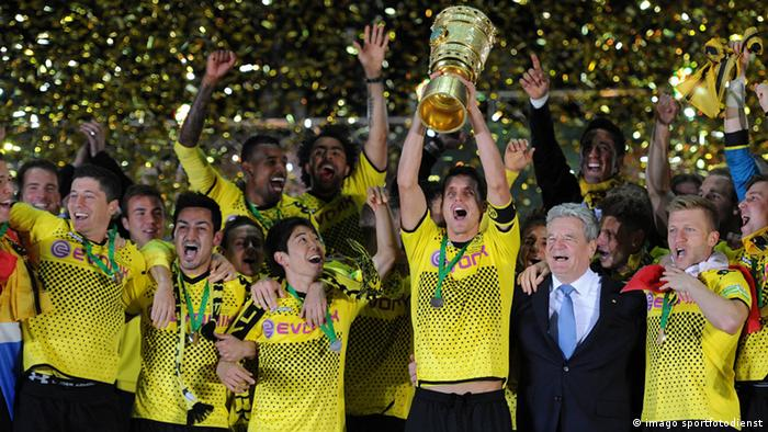 Dortmund captain Sebastian Kehl holds up the German Cup as he celebrates with teammates.