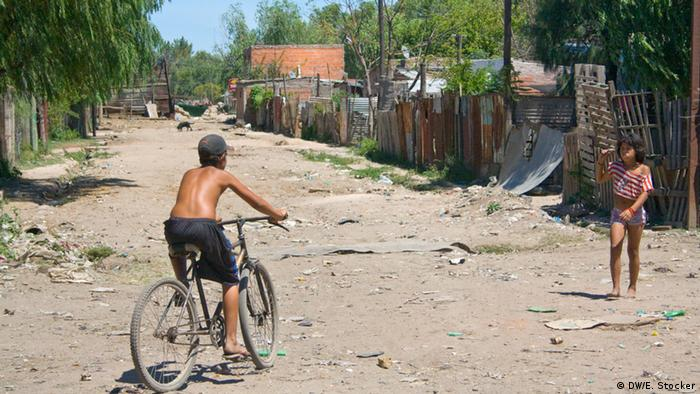Children playing on a dirt road of an impoverished neighborhood in Rosario