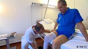 Специалист по реабилитации разрабатывает Геннадию Лисенчуку колено