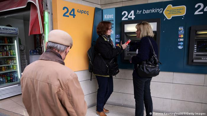 A man waits his turn as women chat in front of the ATM of a bank in the Cypriot capital Nicosia on March 19, 2013. Cyprus was revisiting a bailout package hours before a parliamentary vote on the deal after the eurozone urged a rethink on a controversial levy on bank deposits that sparked outrage at home and roiled global markets. AFP PHOTO/YIANNIS KOURTOGLOU (Photo credit should read Yiannis Kourtoglou/AFP/Getty Images)