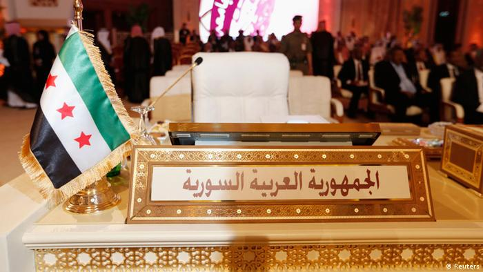 The Syrian opposition flag is seen in front of the seat of the Syrian delegation at the opening the Arab League summit in Doha March 26, 2013. A summit of Arab heads of state opened in the Qatari capital Doha on Tuesday expected to focus on the war in Syria as well as on the Israeli-Palestinian conflict. REUTERS/Ahmed Jadallah (QATAR - Tags: POLITICS)