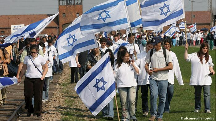 Menschen mit israelischen Fahnen vor der Gedenkstätte Auschwitz.