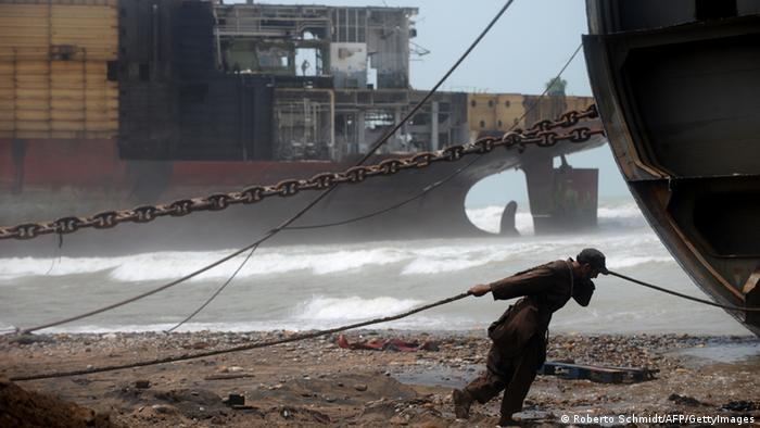A Pakistani shipyard worker pulls on a wire attached to a motor that will help peel away part of the outer structure of a beached vessel being dismantled in one of the 127 ship-breaking plots in Geddani, some 40Kms west of Karachi (Photo: ROBERTO SCHMIDT/AFP/GettyImages)