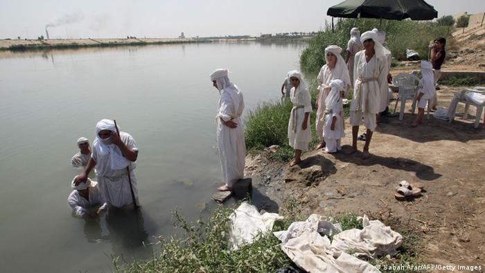 Mandaeans wait to be baptized on the banks of the Tigris River, which runs through the center Baghdad (Photo: SABAH ARAR/AFP/Getty Images)