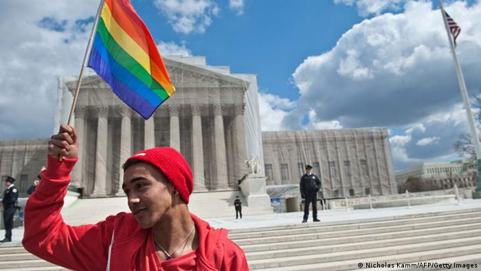 A young man holds a rainbow flag in front of the US Supreme Court in Washington on March 26, 2013 as the court hears arguments on California's Proposition 8 ban on same-sex marriage. AFP PHOTO/Nicholas KAMM (Photo credit should read NICHOLAS KAMM/AFP/Getty Images)