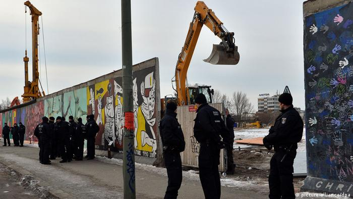 Police stand in front of a gap in the Berlin Wall at the East Side Gallery. Foto: Britta Pedersen/dpa