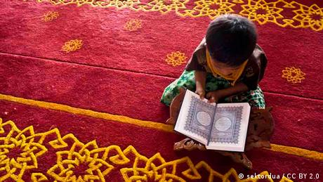A child sits with a Quran on a red carpet