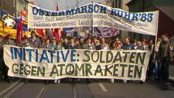 Oster-Demonstranten mit einem großenn Plakat gegen Atomraketen. Foto: dpa/lno