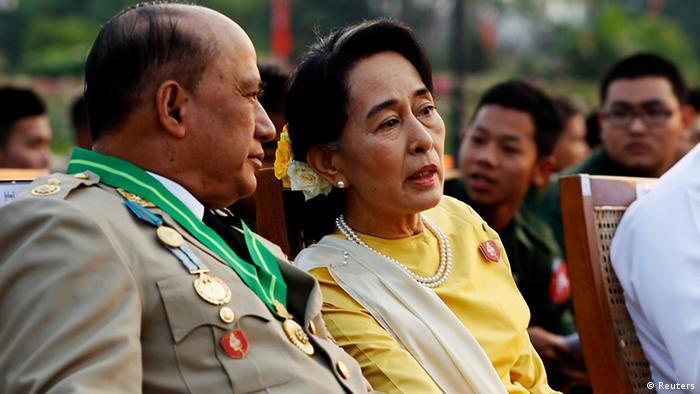 Myanmar's opposition leader Aung San Suu Kyi (R) speaks with Deputy Minister for Border Affairs Major General Zaw Win (L) during the 68th Armed Forces Day in Naypyitaw, March 27, 2013. The event commemorates the Burmese Army's resistance against Japanese occupation in 1945. REUTERS/Nyein Chan Naing/Pool