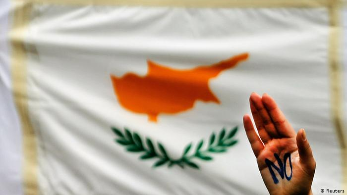A student raises her hand by a Cypriot flag during an anti-Troika protest outside the Presidential palace in Nicosia March 26, 2013. The chairman of Cyprus's biggest commercial bank offered his resignation and thousands of students protested in the capital as banks stayed shut to stop a run on deposits after the island agreed a painful bailout to avert bankruptcy. REUTERS/Yannis Behrakis (CYPRUS - Tags: BUSINESS POLITICS CIVIL UNREST)
