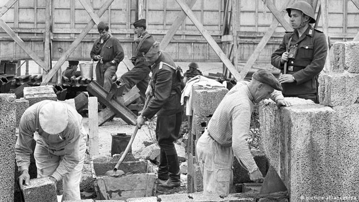 Grenzpolizisten bewachen am 26.05.1962 die Ausbesserungsarbeiten an der Berliner Mauer (Foto: picture-alliance/dpa)