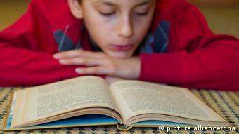 Dječak s glavom oslonjenom na vlastite ruke koncentrirano čita knjigu