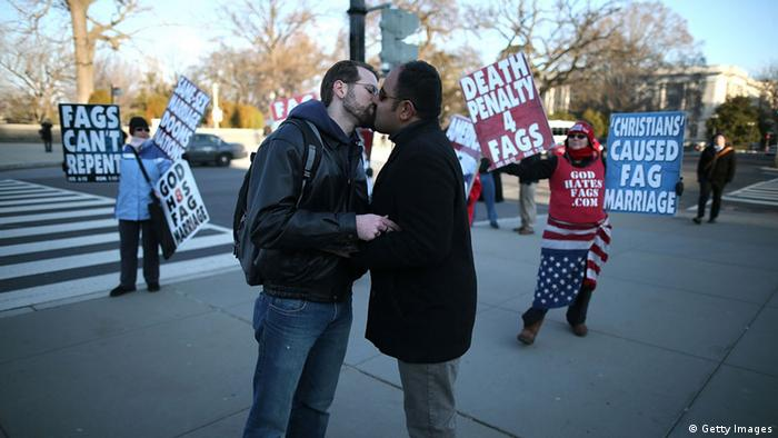 WASHINGTON, DC - MARCH 27: Married couple Nathan Lents (L) and Oscar Cifuentes kiss in front of Westboro Baptist Church protesters, in front of the U.S. Supreme Court, on March 27, 2013 in Washington, DC. Today the high court is scheduled to hear arguments on whether Congress can withhold federal benefits from legally wed gay couples by defining marriage as only between a man and a woman. (Photo by Mark Wilson/Getty Images)