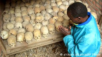 A Rwandan survivor of the 1994 Genocide prays over the bones of genocide victims at a mass grave in Nyamata, Rwanda Tuesday, April 6, 2004. 400 new bodies were recovered in a mass grave in Nyamata, 65 kilometers from Kigali last week. Rwanda is marking the10th anniversary of the genocide that began on April 7, 1994 and in which 500,000 people were killed. (AP Photo/Sayyid Azim) pixel