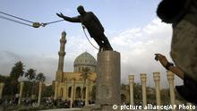 FILE - A U.S. Marine watches a statue of Saddam Hussein being toppled in Firdaus Square in downtown Baghdad on April 9, 2003 file photo. (AP Photo/Jerome Delay, File)