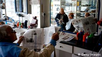 A barber reads a newspaper in his empty shop (Photo: Milos Bicanski/Getty Images)