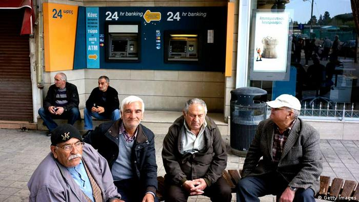A group of men sit outside a bank that has been closed for two weeks (Photo: Milos Bicanski/Getty Images)