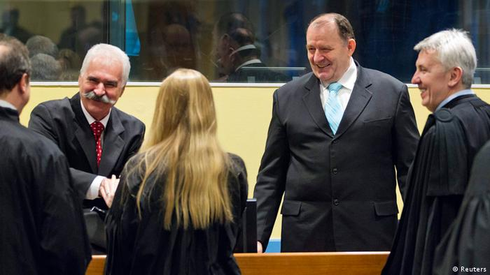 Former high ranking Bosnian Serb official Stojan Zupljanin (2nd L) shakes hands with his lawyer next to Mico Stanisic (2nd R) in the court room as they attend trial at the International Criminal Tribunal for the former Yugoslavia in The Hague March 27, 2013. (Photo: REUTERS/Michael Kooren) (NETHERLANDS - Tags: POLITICS CRIME LAW)