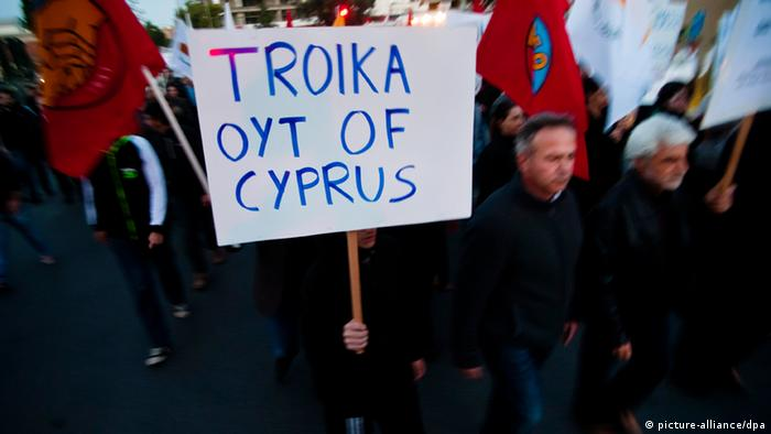 A demonstrator holds up a banner that reads: Troika out of Cyprus Photo: Iakovos Hatzistavrou
