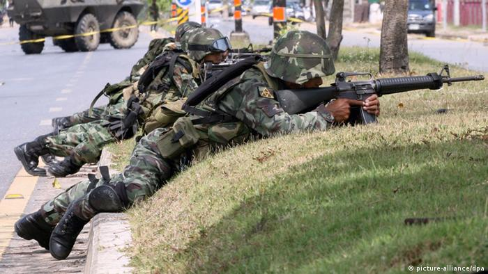 Thai soldiers take their position during the exchange of gunfire with suspected Muslim insurgents in Bannang Sata district of Yala province, southern Thailand, June 27, 2009 (Photo: EPA/NAKHARIN CHINNAWORNKOMOL)