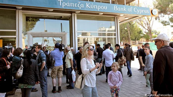 Customers and media representatives waiting outside a branch of the Bank of Cyprus, in Nicosia, Cyprus, in the morning of March 28, 2013 morning. All of the country's 26 banks were open from 12 pm until 6 pm with a withdrawal limit set at 300 euros ($383) per person. Cyprus was braced for the reopening of its banks after nearly two weeks, after the government imposed tough capital controls for at least the next seven days. Police were going from bank to bank in central Nicosia to prevent problems, while dozens of people had started to queue in front of the banks' doors. Copyright: EPA/KATIA CHRISTODOULOU