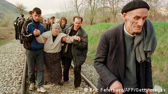 Blace, MACEDONIA: (FILES) Ethnic Albanian refugees arrive by foot in Macedonia, 01 April 1999 after being forced at the Kosovar village of Djeneral Jankovic, to leave a train coming from Pristina in Kosovo. Top Serbian and Kosovo Albanian leaders were gearing up for their first face-to-face talks in Vienna 24 July 2006, seven years after the war, to discuss the future status of the independence-seeking province. The unprecedented meeting will be the first between top Serbian and Kosovo Albanian leaders since 1999, when a NATO bombing campaign forced Serbian troops to pull out of the province and end a crackdown on armed ethnic Albanian separatists. AFP PHOTO FILES ERIC FEFERBERG (Photo credit should read ERIC FEFERBERG/AFP/Getty Images)