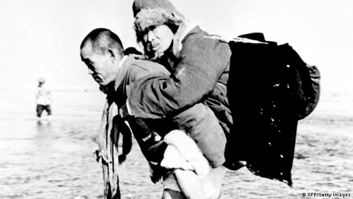 A Korean civilian carries his father on his back as they cross the Han river 30 January 1951. (Photo: AFP/Getty Images)