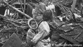 circa 1950: An elderly woman and her grandchild wander among the debris of their wrecked home in the aftermath of an air raid by U.S. planes over Pyongyang, the Communist capital of North Korea. (Photo by Keystone/Getty Images)